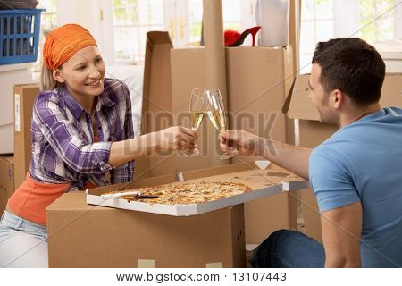 Happy couple having pizza and champagne to celebrate moving house.?