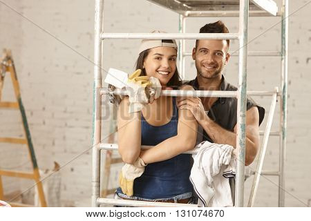 Happy young loving couple renovating home, embracing under scaffold, looking at camera.