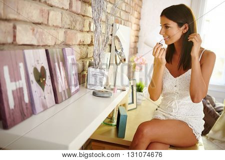 Young woman looking at herself in mirror applying lipstick at home.
