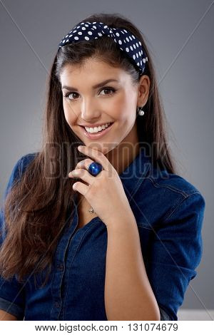 Pretty girl smiling with hand on chin, looking at camera.