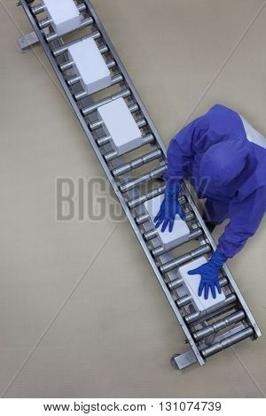 aerial view of worker in blue uniform working with boxes on packing line