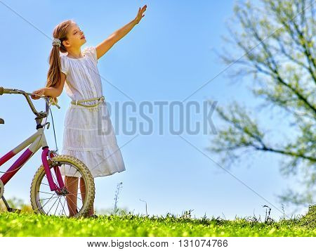 Bikes bicycling girl. Child girl wearing white skirt hand up and pleased near to bicycle. Girl looks away. Blue sky and green tree on background. Rural holiday. Summer park outdoor.