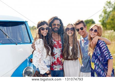 summer holidays, road trip, vacation, travel and people concept - smiling young hippie friends hugging over minivan car
