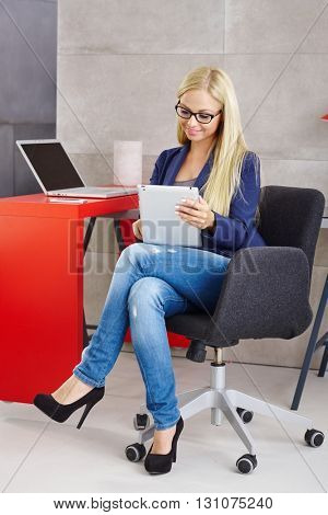 Busy blonde woman using tablet computer sitting at desk.