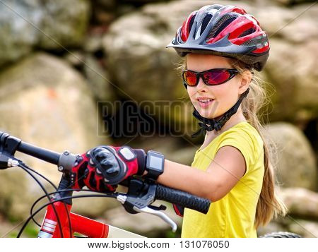 Bikes bicyclist girl. Girl with  smart watch rides bicycle into mountains. Girl wearing helmet and gloves on bicycle in mountaineering  . Mountaineering  is good for health.