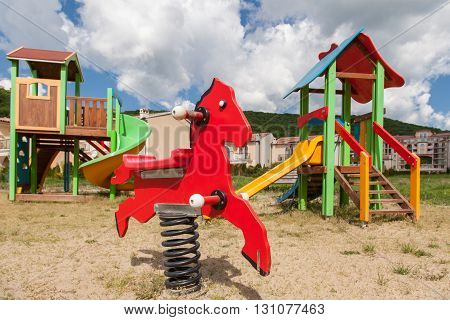 Children's playground in the park. Little red horse