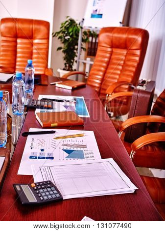 Business interior with four leather chairs in office. There are bottles water on the table.