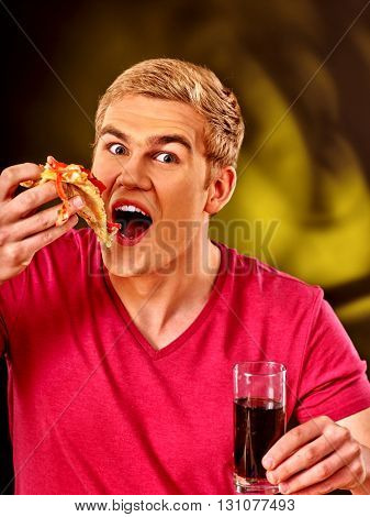Young man eating slice of pizza . Fastfood concept.