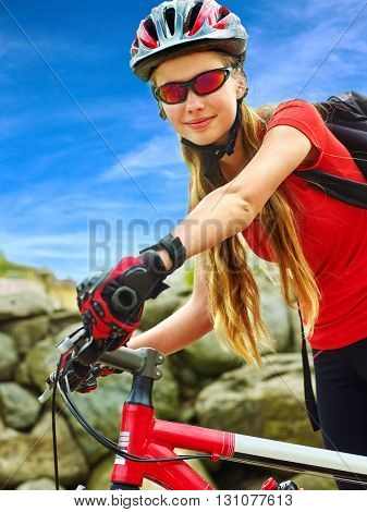 Bikes bicyclist girl. Girl wearing smart watch rides bicycle into mountains. Girl on bicycle in mountaineering  . Girl clings to wheel and looking at the camera.