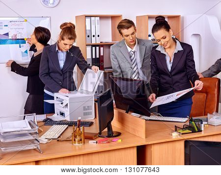 Happy group business people in office. Woman is printing out.
