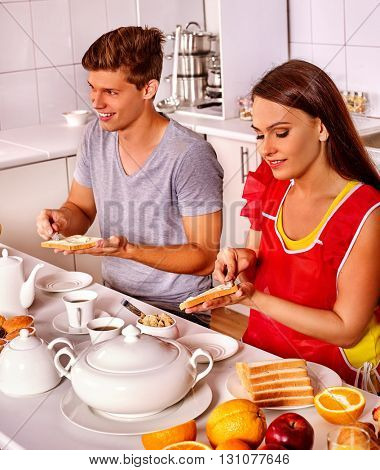 Happy young couple have breakfast at home kitchen.