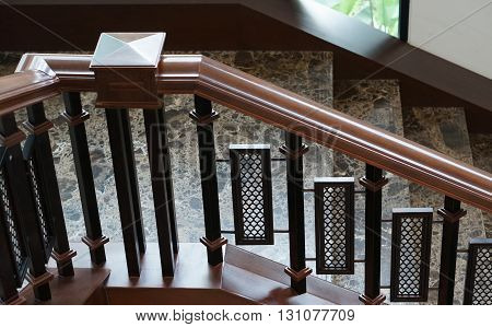 Elegant stairs with handrail decorated by stone and wood in the house.