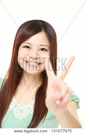 portrait of young Japanese woman showing a victory sign on white background