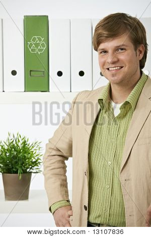Portrait of young environmentalist man posing in front of shelf in office, recycling logo on green folder.?