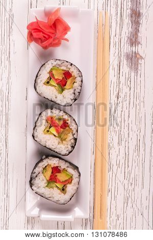 Japanese food. Vegetable rolls with ginger and chopsticks on white wooden table. Top view