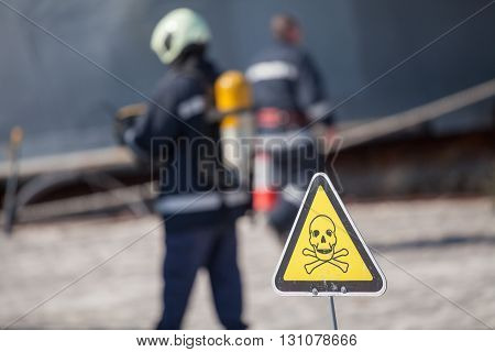 danger sign with skull and crossbones firefighters on background