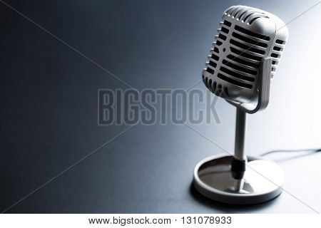 the classic vintage silver microphone on black table