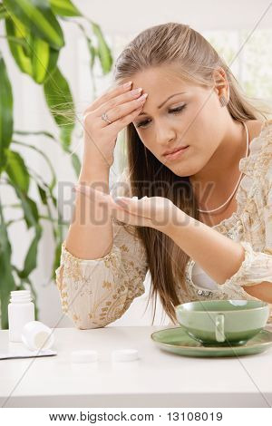 Young woman having headache, holding her head and looking at pills in hand.