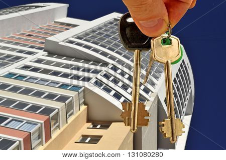 The keys to the apartment in hand on the background of new homes