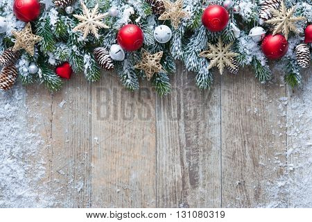 Christmas background with decorations and snow on wooden board