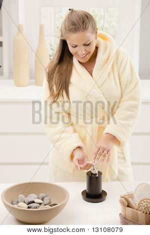 Young woman wearing bathrobe washing hands at home in bathroom, smiling.