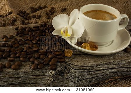 Coffee cup and white orchid on the wooden background. Coffee break. Morning coffee. Cup of coffee. Coffee cup. Coffee