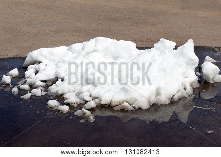 A large pile of dirty white snow lies on the asphalt road (The snow lies in a puddle)