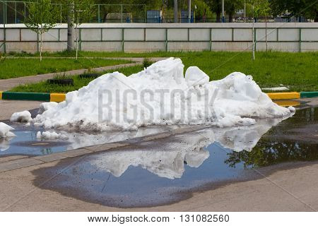 A large pile of dirty snow lying in the puddle on the asphalt road on background green grass and white fence