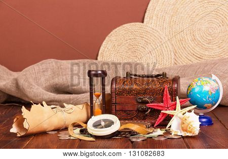 Old map, treasure chest, compass, globe and hourglass on brown background.