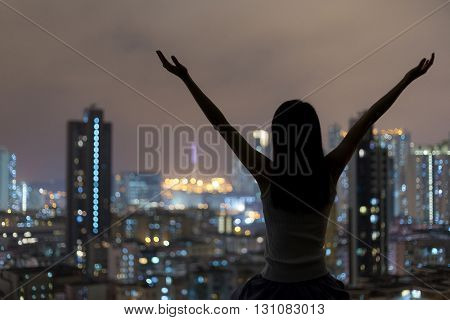 Silhouette of woman arms raised up to sky in city at night