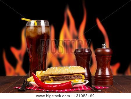 Fast Food: cola, a hamburger, french fries and spices on a background of flames.