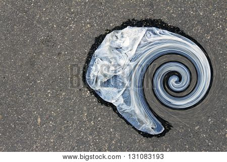 Wet plastic bag lying on the asphalt rolled into a spiral