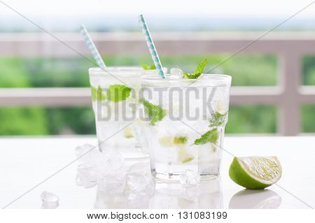 Non alcohol cold mojito cocktail with fresh lime mint and crushed ice on a white table closeup