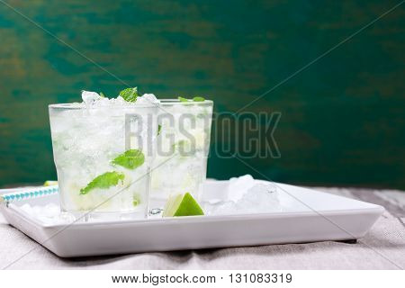 Non alcohol cold mojito cocktail with fresh lime mint and crushed ice on a white plate on a vintage wooden background closeup horizontal with place for text