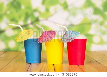 Multi-colored disposable paper cups and straws on abstract green background.
