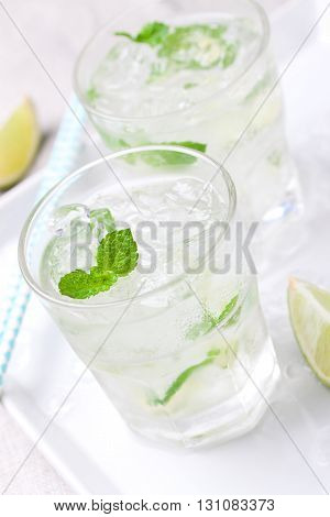 Non alcohol cold mojito cocktail with fresh lime mint and crushed ice on a kitchen background closeup