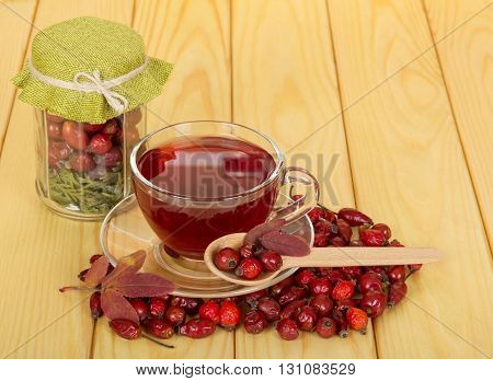 Bank with dried fruits rose hips and a cup of tea on a background of light wood.