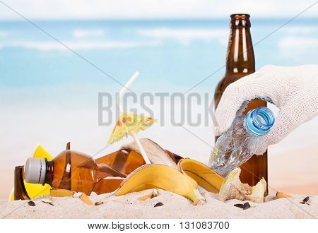 Glass bottle and plastic, food waste in the sand against the sea.