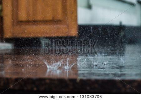 heavy rain drops falling on city asphalt during downpour.