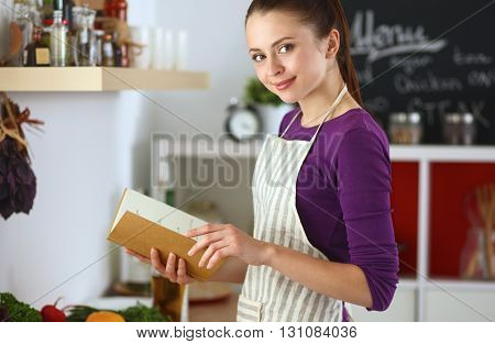 A young woman standing in the kitchen reading a cookbook