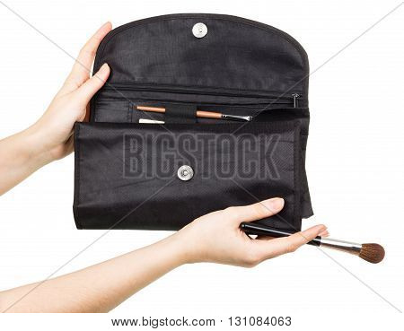 Black Carrying Pouch with brushes for make-up in female hands isolated on white background.