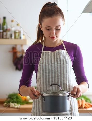A young woman standing in her kitchen and holding a saucepan