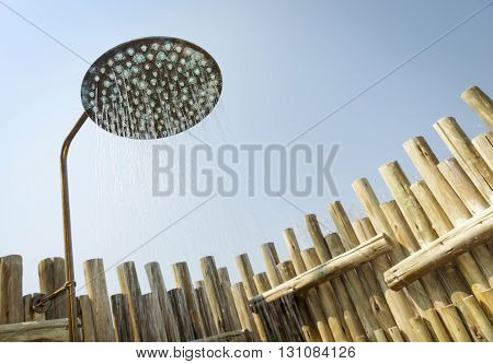 Outdoor shower with water coming out of the head and blue sky behind