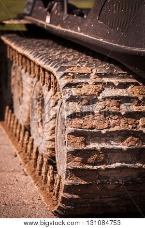 Close up of a caterpillar track full of mud.
