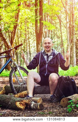 Cyclist with backpack smiling young man has happiness emotion shows thumb up in beautiful forest summertime journey