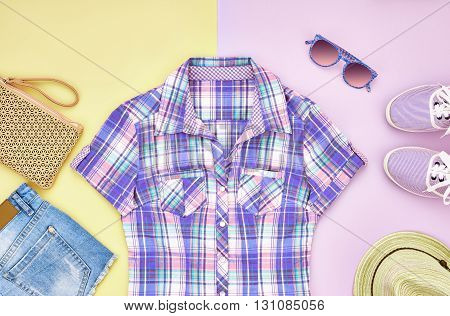 Street style Fashion girl clothes accessories set. Hipster woman, trendy handbag, plaid shirt, denim, gumshoes, hat and sunglasses. Urban creative outfit.Overhead, top view on pink yellow background