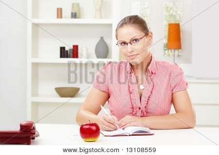 Happy young woman sitting at table writing in diary book, smiling.