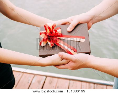 Couple Giving A Gift Box To Each Other. Happy Relationship In Outdoor Scene. Love And Relationship C