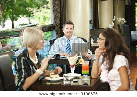 Businessman using laptop in cafe, young woman eating sweets and talking in the foreground. Selective focus on businessman.