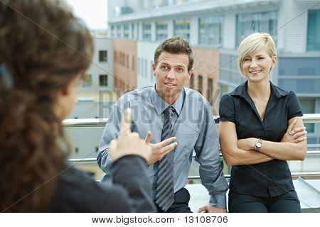Empresarios hablando en la terraza del edificio de oficinas. En la vista del hombro.